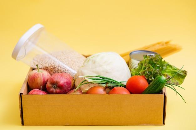 Divers aliments dans une boîte en carton, le concept de don.