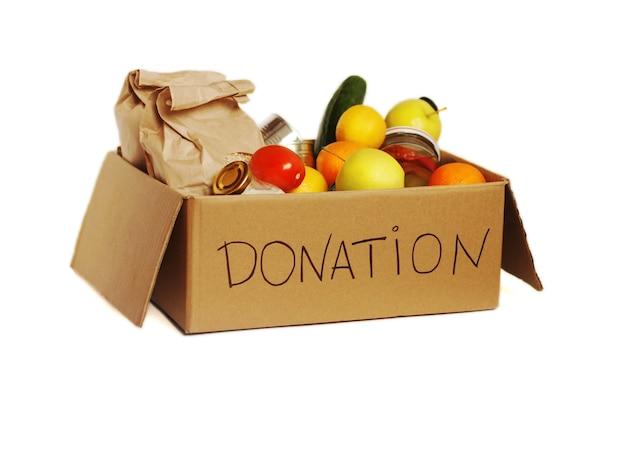 Divers aliments dans une boîte de dons en carton, isolés.