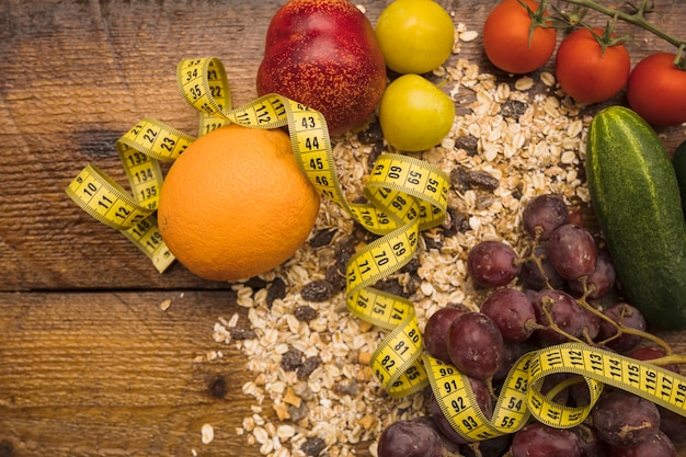 Divers aliments sains avec du ruban à mesurer sur fond en bois