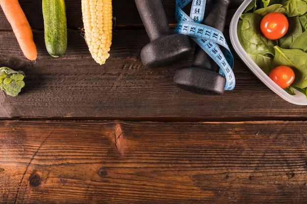 Divers aliments sains avec ruban à mesurer et haltère sur toile de fond en bois