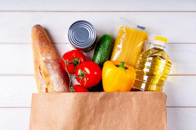 Divers aliments sains, tomates, pain, pâtes, concombre, huile et poivre dans un sac en papier sur fond blanc. concept de livraison de nourriture avec un espace pour le texte.