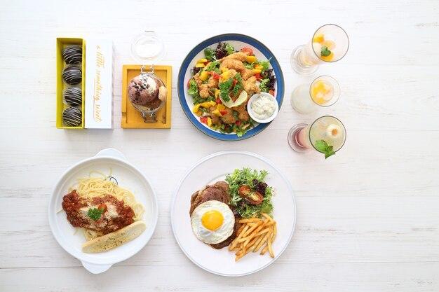 Divers aliments sur la table avec oeuf, gâteaux, crème glacée, cocktail, spaghettis, viande, frites et sauce