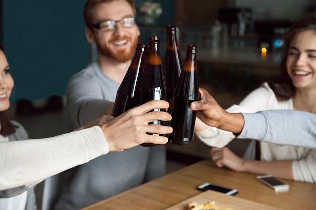 Divers amis cliquetant des bouteilles de bière artisanale dans un pub