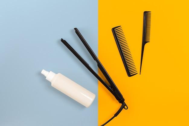 Divers appareils de coiffure sur fond de papier bleu et jaune, vue de dessus. espace de copie. nature morte. maquette. mise à plat