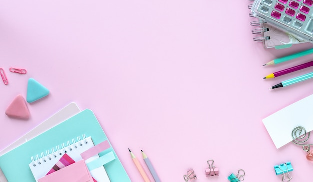 Divers articles de papeterie colorés pour l'école et le bureau sur fond rose avec copyspace.