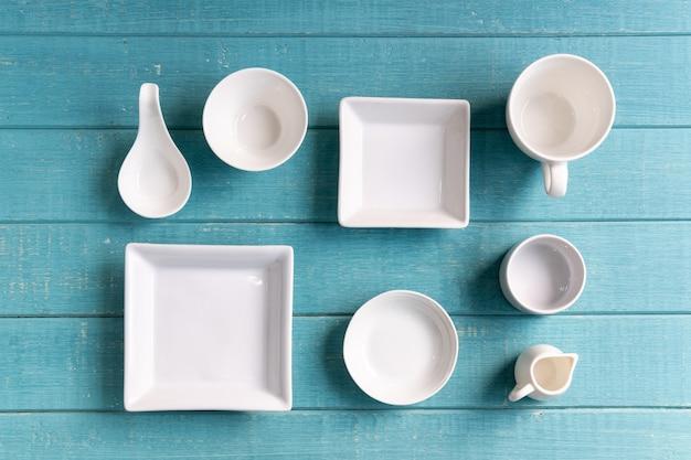 Divers assiettes blanches vides et bols sur fond en bois, vue de dessus