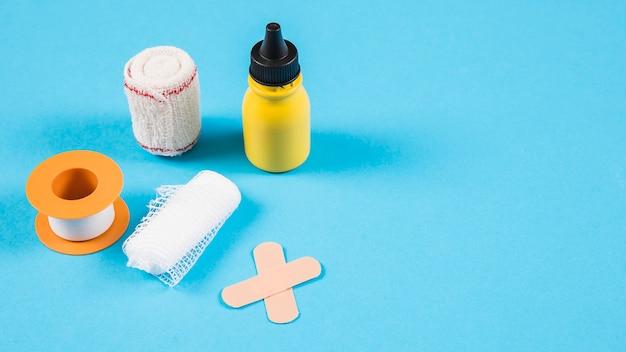 Divers bandages avec une bouteille jaune sur fond bleu