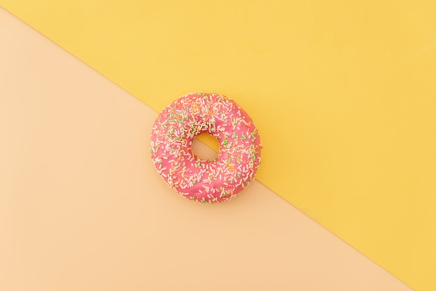 Divers beignets décorés en mouvement tombant sur fond rose. beignets sucrés et colorés tombant ou volant en mouvement.