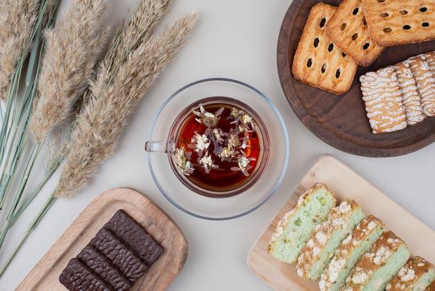 Divers biscuits, tranches de gâteau et tasse de thé sur blanc.