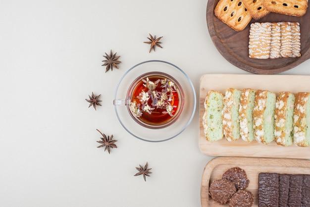 Divers biscuits, tranches de gâteau et tasse de thé sur une surface blanche