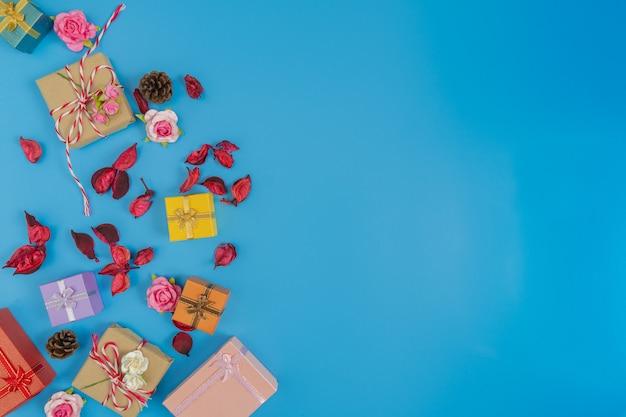 Divers de boîte-cadeau avec des feuilles rouges séchées et pomme de pin sur fond bleu