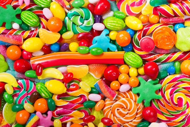 Divers bonbons colorés, gelées, sucettes et marmelade en arrière-plan, vue du dessus