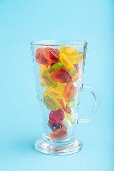 Divers bonbons à la gelée de fruits dans un verre à boire sur fond pastel bleu