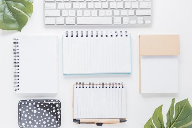 Divers cahiers et clavier sur un bureau blanc