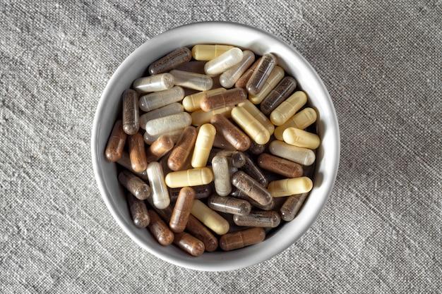 Divers capsules médicales à base de plantes et homéopathiques dans un bol blanc