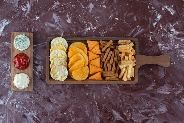 Divers chips sur plateau de service avec sauce , sur la table en marbre.