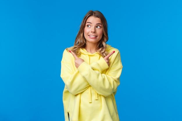 Divers choix, je ne peux pas décider. jolie fille blonde rêveuse en sweat à capuche jaune faisant son choix, pointant les doigts sur le côté à gauche et à droite et souriant, choisissant une chose parmi tous, sur un mur bleu