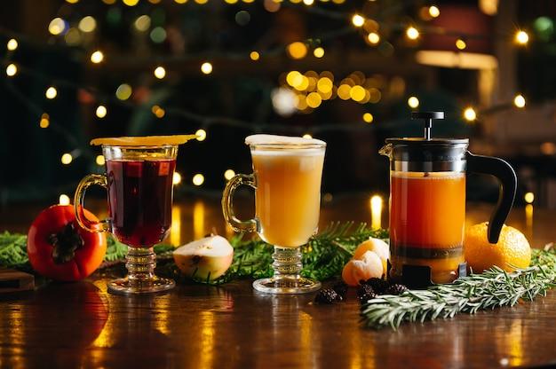Divers cocktails chauds à l'alcool de saison d'automne ou d'hiver. thé à la mandarine en presse française, cidre de poire chaud et vin chaud au kaki