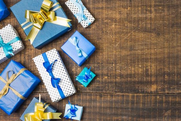 Divers coffrets cadeaux emballés et décorés de rubans sur une vieille table patinée