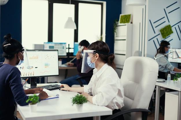 Divers collègues regardant un écran d'ordinateur avec un graphique économique portant un masque facial contre covid19. équipe multiethnique travaillant en entreprise avec une nouvelle norme respectant la distance sociale pendant la pandémie mondiale
