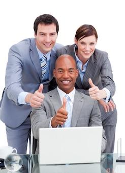 Divers collègues de travail avec des thums sur un ordinateur portable