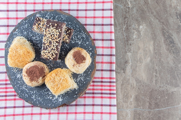 Divers desserts sur une planche sur torchon sur marbre.