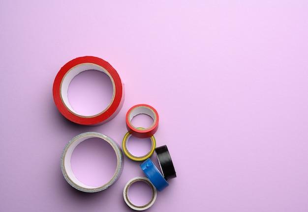 Divers écheveaux de scotch multicolore et ruban électrique sur fond violet, copy space