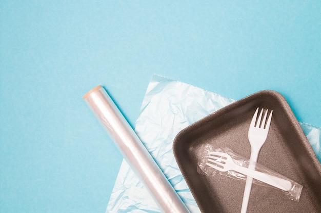 Divers emballages en plastique jetables sur fond bleu, un plateau de nourriture, un rouleau de ruban adhésif en plastique et un sac pour congeler les aliments, une fourchette jetable et un tube à boire, concept de pollution de l'environnement