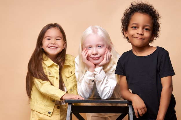 Divers enfants positifs souriants posant heureux ensemble