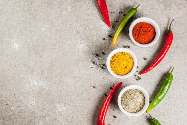 Divers épices et assaisonnements. cuisine . curcuma, curry, paprika, poivre, piment, basilic séché, sel, piment frais, thym. pierre grise . vue de dessus