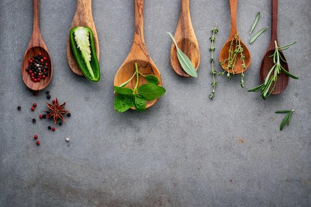 Divers des épices et des herbes dans des cuillères en bois.