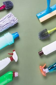 Divers équipements de nettoyage disposés dans une rangée sur fond vert