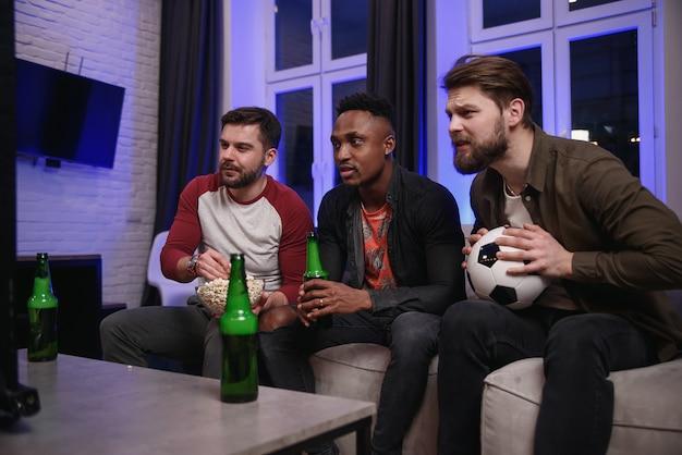 Divers fans de football applaudissant l'équipe favorite et buvant de la bière à la maison, copie espace