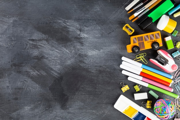 Divers fournitures de bureau et de peinture sur fond noir.