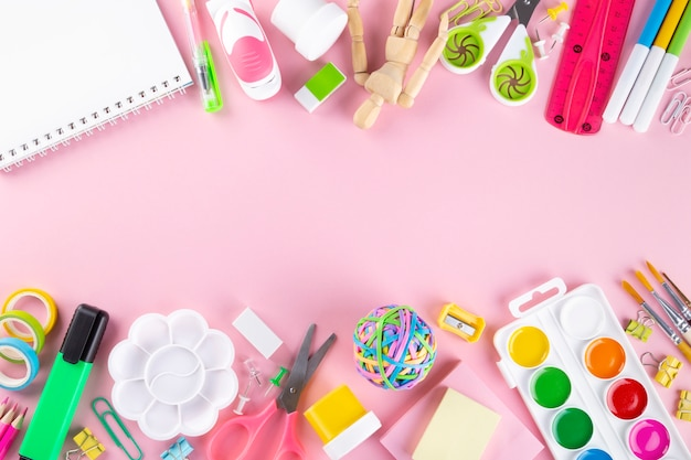Divers fournitures de bureau et de peinture sur fond rose.