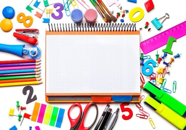Divers fournitures scolaires isolées sur fond blanc, bloc-notes au centre du cadre concept à l'école