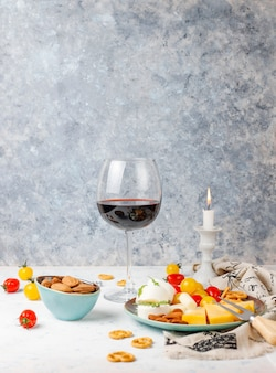 Divers fromages et assiette de fromages sur table lumineuse avec différents fruits à coque et fruits et verre de vin