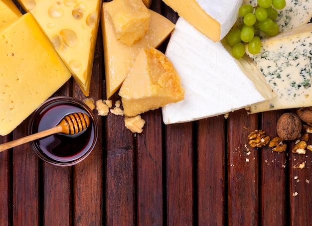 Divers fromages sur table en bois avec espace vide.