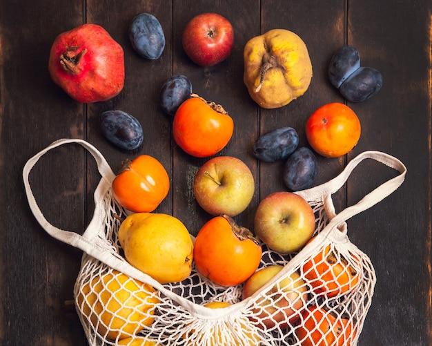 Divers fruits d'automne dans un sac en filet sur un fond en bois foncé.