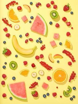 Divers fruits et baies frais sur fond jaune, vue de dessus