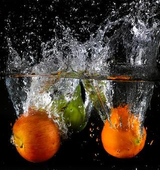 Divers fruits éclaboussent dans l'eau
