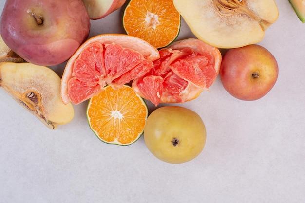 Divers fruits frais sur tableau blanc.