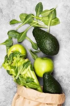 Divers fruits et légumes verts - céleri, pommes, avocat, épinards dans un emballage en papier sur un fond clair. vue de dessus. contexte alimentaire.