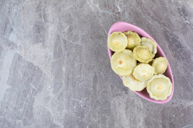 Divers fruits marinés dans un bol rose.