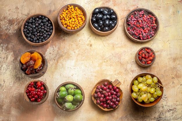 Divers fruits naturels et frais dans de petits pots en bois marron