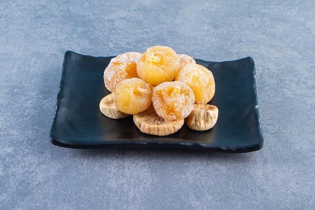 Divers fruits secs dans un bol sur un dessous de plat sur la surface en marbre