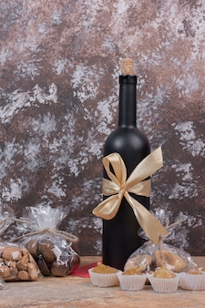 Divers fruits secs et noix emballés dans un sac en plastique et une bouteille de vin.