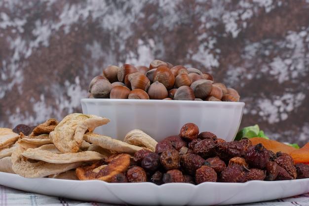 Divers fruits secs et noix sur plaque blanche.