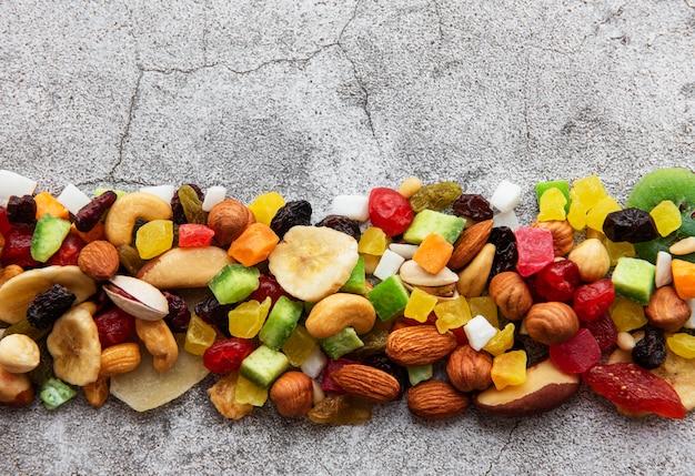 Divers fruits secs et noix sur une surface de béton gris