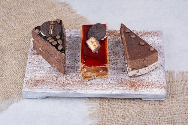 Divers gâteaux sucrés sur planche de bois avec toile de jute. photo de haute qualité